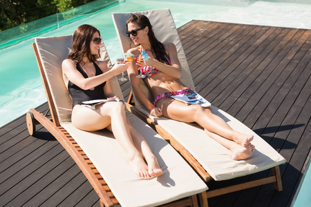 Two beautiful young women toasting drinks by swimming pool photo