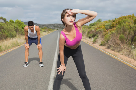Fit young couple running on the open road together photo