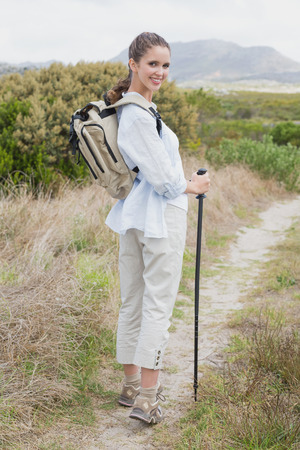 Portrait of a smiling young woman standing on countryside landscape photo