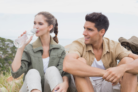 Young couple taking a break after hiking uphill photo