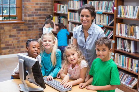 early: Cute pupils and teacher looking at computer in library at the elementary school