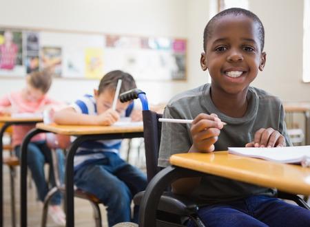 children: Инвалидов ученик улыбка на камеру в классе в начальной школе