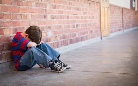 Sad pupil sitting alone in corridor at the elementary school Stock Photo