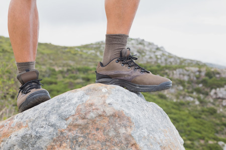 adventuring: Close up low section of a hiking man standing on rock against mountain terrain Stock Photo