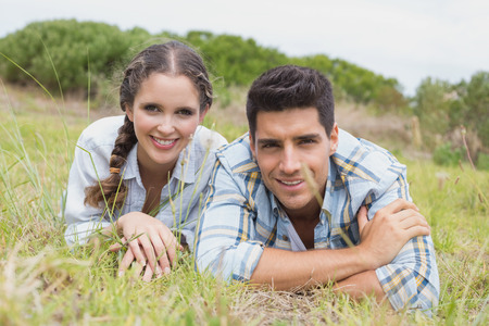 adventuring: Close up portrait of a young couple lying on countryside landscape Stock Photo