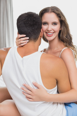 Loving relaxed young couple together in bed at home photo