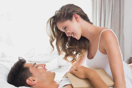 Side view of romantic young couple in bed at home photo