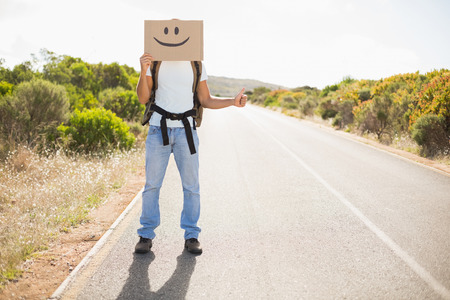 escapism: Full length of a man with smiley face hitchhiking on countryside road