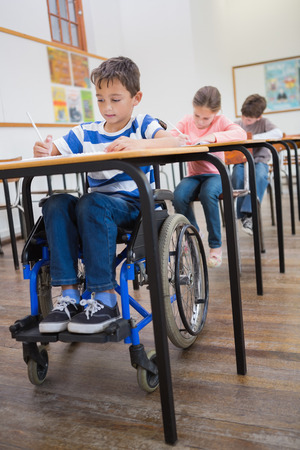 Disabled pupil writing at desk in classroom at the elementary school Stock Photo
