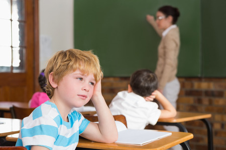Cute pupil not paying attention in classroom at the elementary school photo
