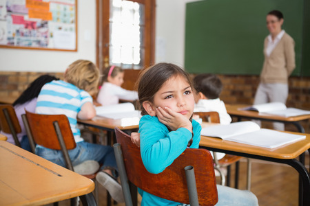 Thoughtful pupil sitting at her desk at the elementary school photo