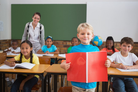 Cute pupils smiling at camera in classroom at the elementary school photo