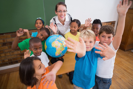 Cute pupils smiling around a globe in classroom with teacher at the elementary school photo