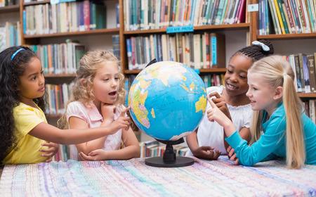 niños negros: Alumnos lindos que miran el globo en la biblioteca en la escuela primaria Foto de archivo