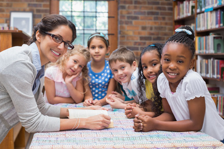 Cute pupils and teacher reading in library at the elementary school Stock Photo