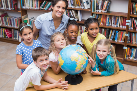 Cute pupils and teacher looking at globe in library at the elementary school photo