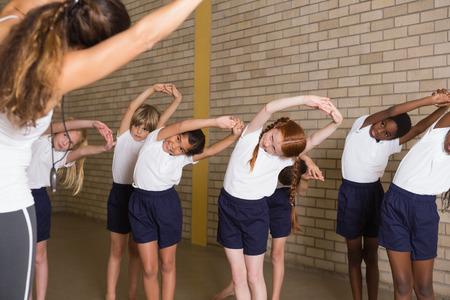 educacion fisica: Alumnos lindos que calientan en uniforme de educaci�n f�sica en la escuela primaria