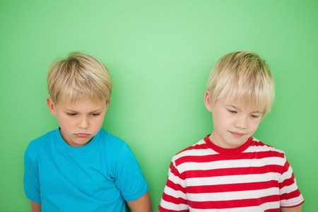 bleakness: Sad little boys looking down on green background