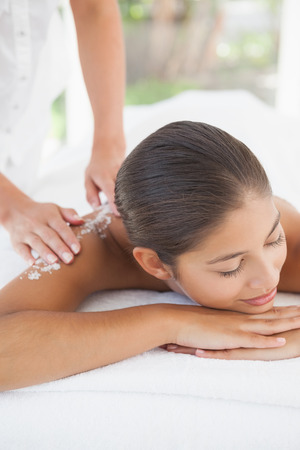 Beautiful brunette lying on massage table with salt scrub on back at the health spa photo