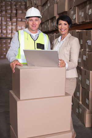 Warehouse worker and manager using laptop in a large warehouse photo