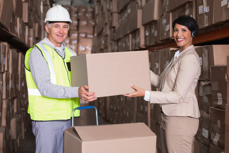 Warehouse worker and manager passing a box in a large warehouse photo