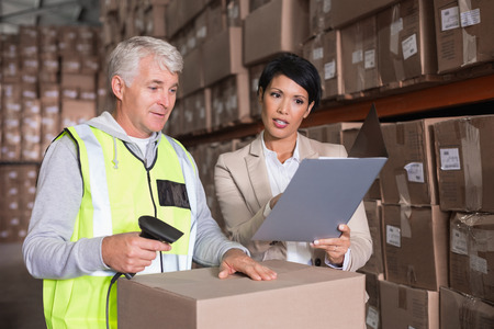 Warehouse worker scanning box with manager in a large warehouse photo