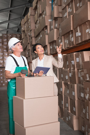 Warehouse worker scanning box with manager holding tablet pc in a large warehouse photo