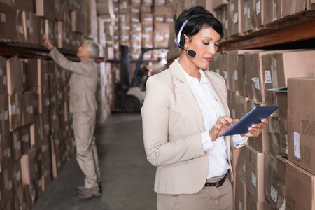 warehouse: Pretty warehouse manager using tablet pc in a large warehouse Stock Photo