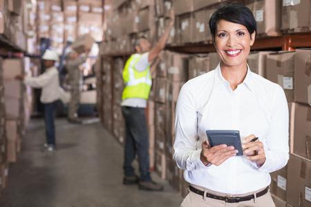 Pretty warehouse manager te openen met de rekenmachine in een groot magazijn