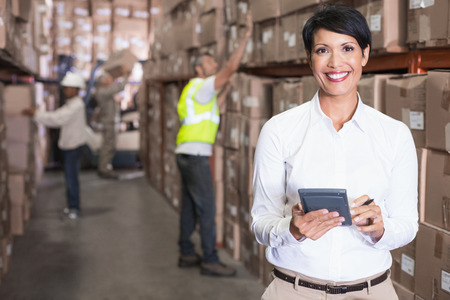Pretty warehouse manager using calculator in a large warehouse photo