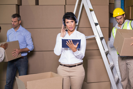 Pretty warehouse manager using tablet during busy period in a large warehouse photo