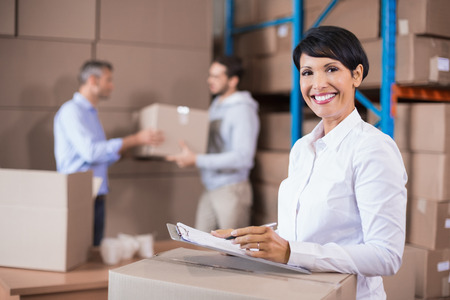 shutting: Warehouse manager writing on clipboard in a large warehouse