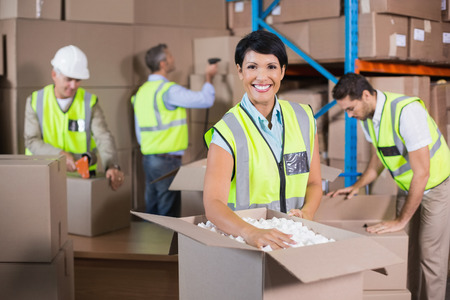 Warehouse workers in yellow vests preparing a shipment in a large warehouse Stock Photo