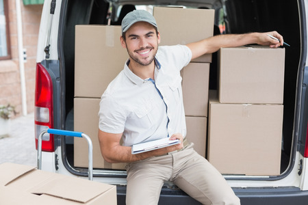 Delivery driver writing in clipboard outside the warehouse Stock Photo