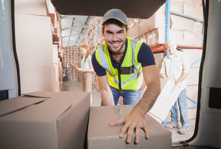 warehouse: Delivery driver loading his van with boxes outside the warehouse Stock Photo