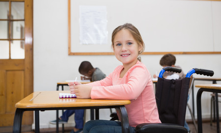 elementary school: Disabled pupil smiling at camera in classroom at the elementary school