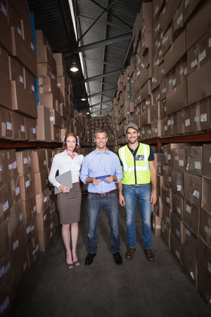 Warehouse team smiling at camera in a large warehouse photo