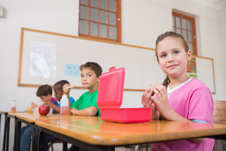Cute pupils having their lunch in classroom at the elementary school photo