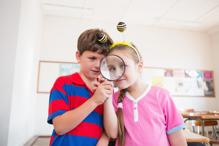 hairband: Cute pupils looking through magnifying glass at the elementary school