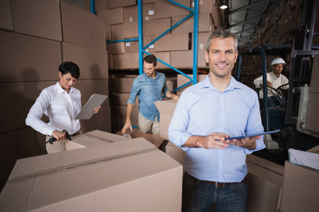 Warehouse manager using his tablet pc in a large warehouse photo