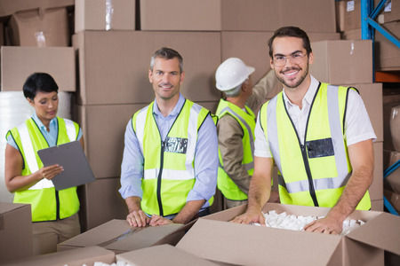 sealing tape: Warehouse workers in yellow vests preparing a shipment in a large warehouse Stock Photo
