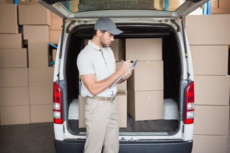delivery driver: Delivery driver checking his list on clipboard in a large warehouse Stock Photo
