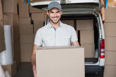 Delivery driver smiling at camera holding box in a large warehouse