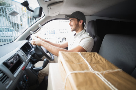 Delivery driver driving van with parcels on seat outside the warehouse photo