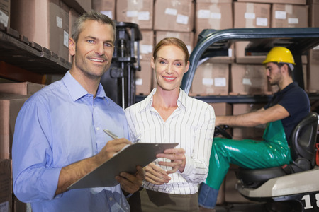 Warehouse team working together with clipboard in a large warehouse photo