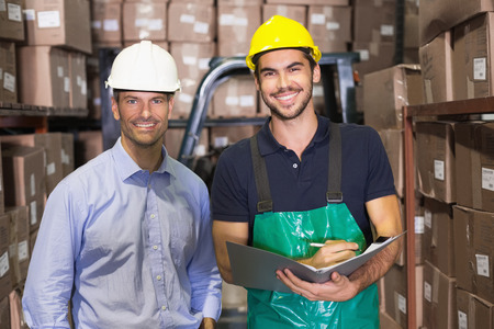 Warehouse manager and foreman smiling at camera in a large warehouse photo