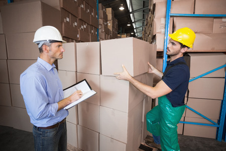 Warehouse worker loading up a pallet with manager in a large warehouse photo