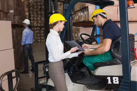 co operating: Warehouse manager talking with forklift driver in a large warehouse