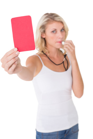 Portrait of young woman blowing whistle and holding red card on white background photo