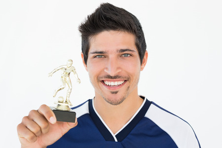 Football player holding winners trophy over white background photo